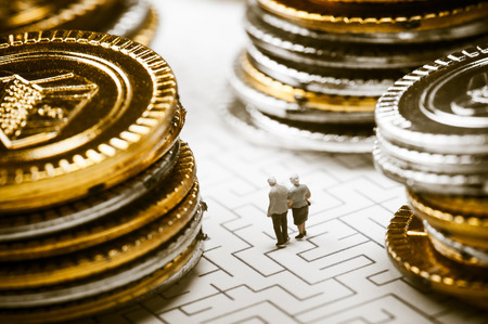 money problems: Couple of elderly walk through the maze, money problems