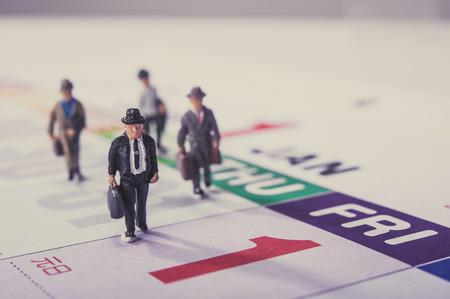 Miniature d'affari che cammina sul calendario