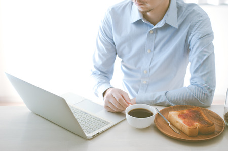 busy beard: Japanese man who is operating a laptop while eating breakfast Stock Photo