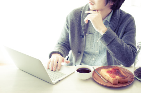 sideline: Japanese man who is operating a laptop while eating breakfast Stock Photo