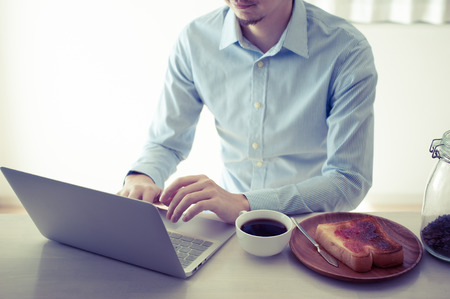 Japanese man who is operating a laptop while eating breakfast