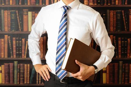 たくさんの本の前に立つビジネスマン 写真素材