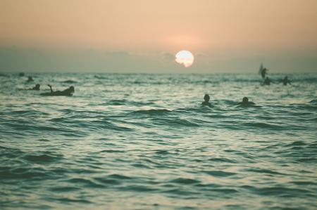 夕日とサーファーのシルエット