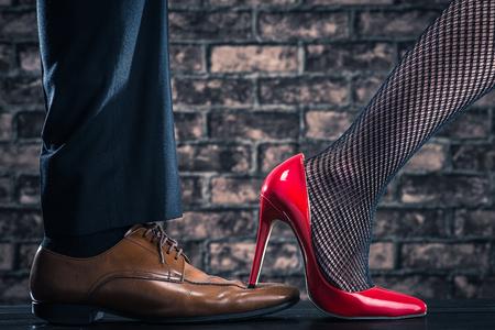 las mujeres de tacón alto están intensificando en los zapatos del hombre Foto de archivo