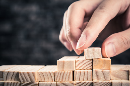 business game: The hand of man has piled up a wooden block Stock Photo
