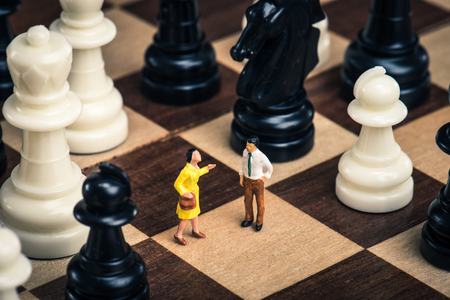 dating strategy: Miniature man standing on the chessboard