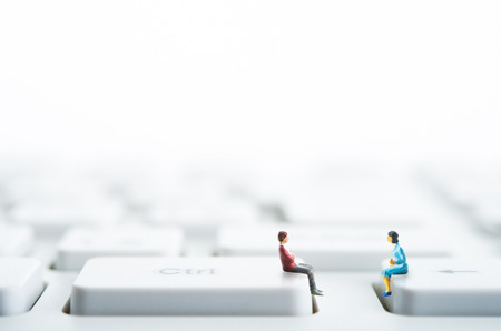 Men and women sitting on top of the computer keyboard