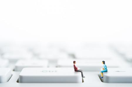 Männer und Frauen sitzen oben auf der Computer-Tastatur