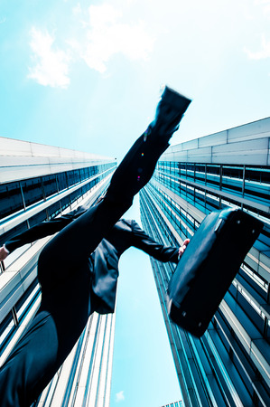 low angle: Businessman jumping over the camera, low angle, building background