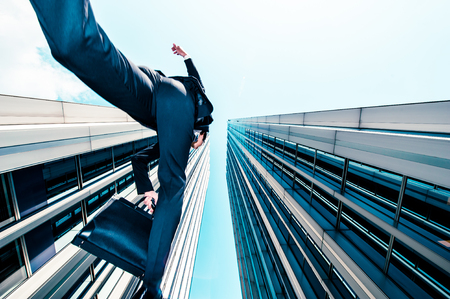 men at work: Businessman jumping over the camera, low angle, building background