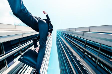 Zakenman springen over de camera, lage hoek, gebouw achtergrond