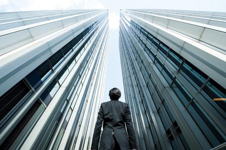 Zakenman en keek naar de hoge bouw, lage hoek Stockfoto