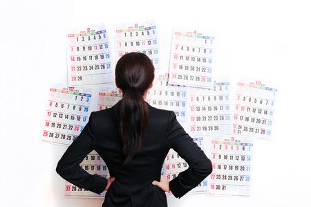 Businesswoman suffering in front of the calendar Stok Fotoğraf