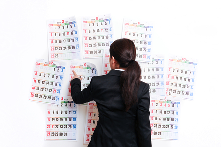 remorse: Businesswoman suffering in front of the calendar Stock Photo