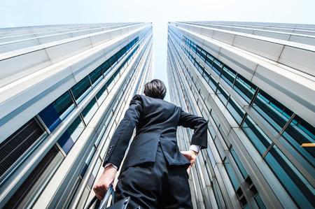El hombre de negocios mirando hacia arriba en el alto edificio, bajo ángulo