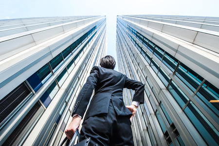 Unternehmer suchen nach oben auf dem hohen Gebäude, low angle