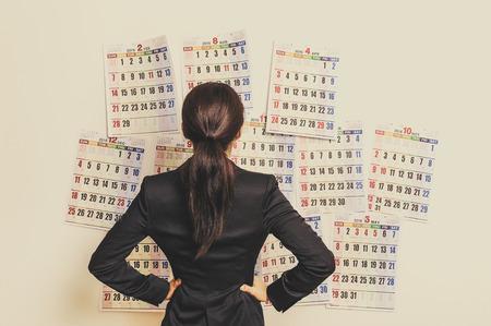 Businesswoman suffering in front of the calendar Standard-Bild