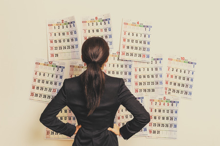Businesswoman suffering in front of the calendar Stockfoto