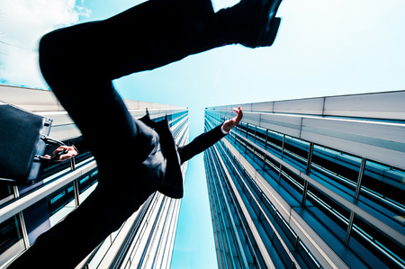 Businessman jumping over the camera, low angle, building background