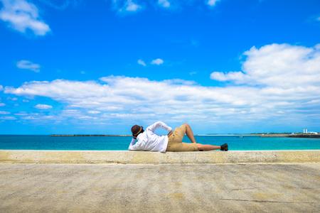 slowly: Hombre que duerme en la playa Foto de archivo