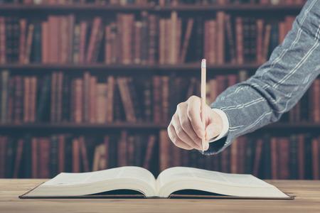 厚い本、ペンを持っている手