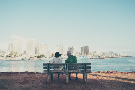 A couple of elderly people sitting on the beach