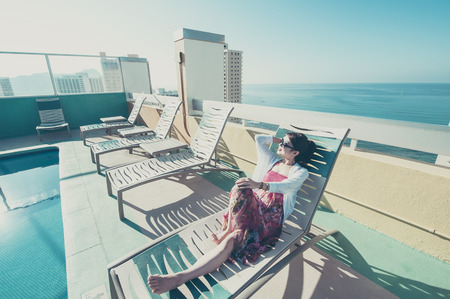 rich people: Asian women who are relaxing by the pool of a resort hotel Stock Photo