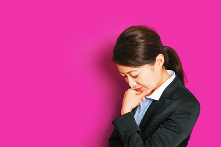 Troubled business woman, pink background Stock Photo