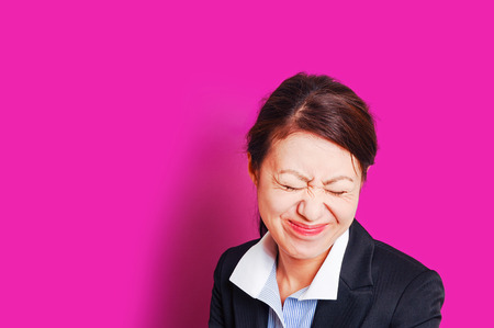 relaciones laborales: Troubled business woman, pink background Foto de archivo