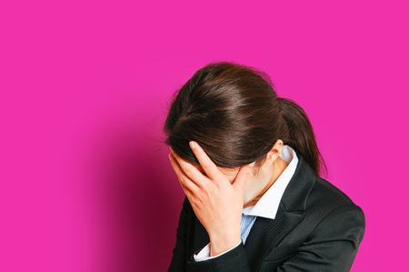 human relations: Troubled business woman, pink background Stock Photo