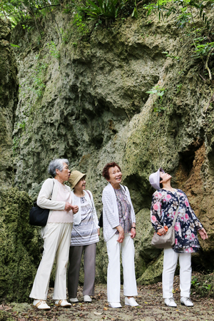 asian style: Elderly woman four people are walking the rocky Stock Photo