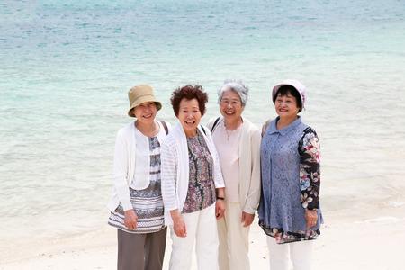 Elderly woman standing on the beach