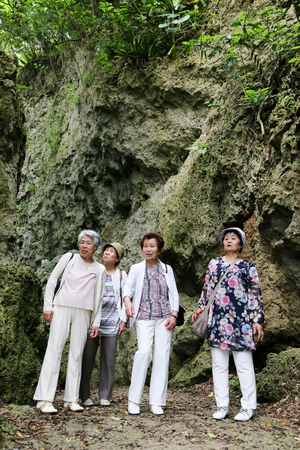 four people: Elderly woman four people are walking the rocky Stock Photo