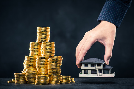 Una gran cantidad de dinero y modelo de casa Foto de archivo - 71687342