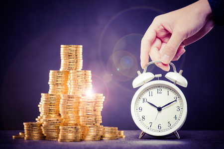 A large amount of money and alarm clock Stock Photo