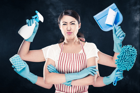 Angry housewife and cleaning tools Stock Photo