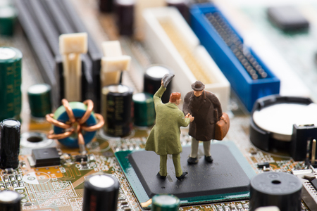 Miniature person are shaking hands on a computer motherboard Stock Photo