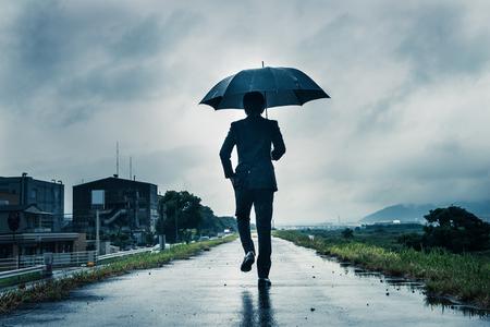businessman are holding an umbrella, dark image