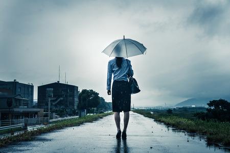 De vrouw houdt een paraplu, donker beeld Stockfoto