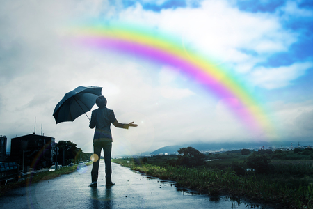 Zakenman met een paraplu, regenboog en lucht na de regen