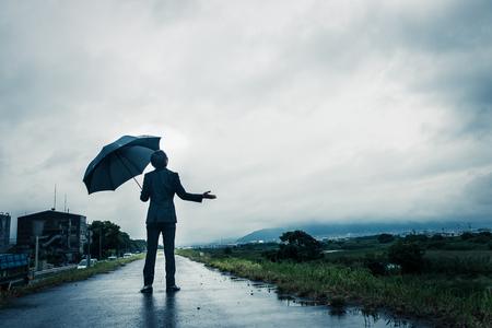 ビジネスマンは、傘、暗いイメージを保持しています。