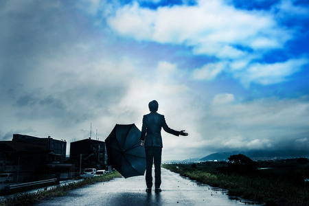 Businessman holding an umbrella, the sky after the rain Stock Photo
