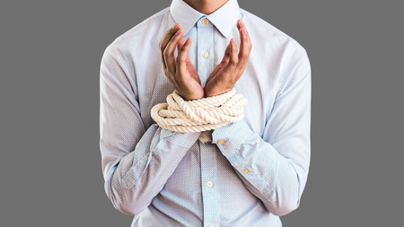 Businesspeople who are tied up with ropes