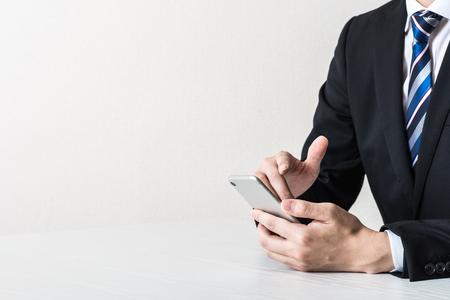 Businessman operating a smartphone