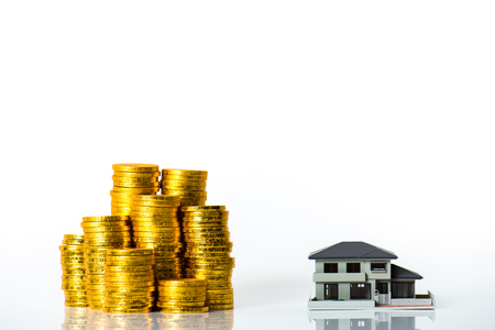 house exchange: House model and lots of gold coins, white background Stock Photo