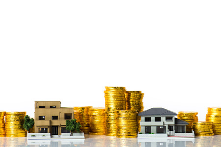 Modelo de la casa y un montón de monedas de oro, fondo blanco Foto de archivo - 80679070