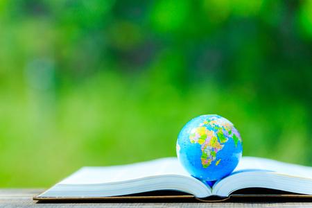 De wereldbol geplaatst op het boek en groene achtergrond wazig Stockfoto
