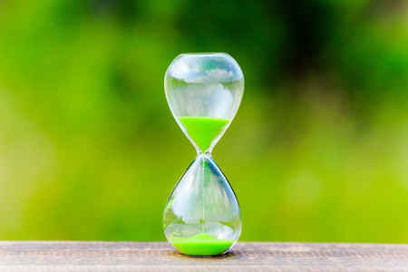 Hourglass and green blur background