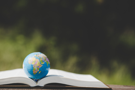 law school: The globe placed on the book and green blur background Stock Photo