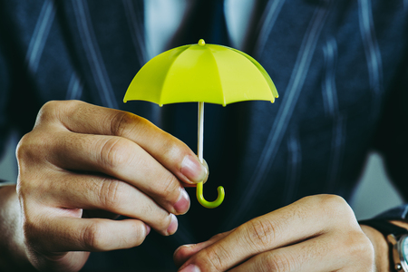 businessman holding a yellow umbrella